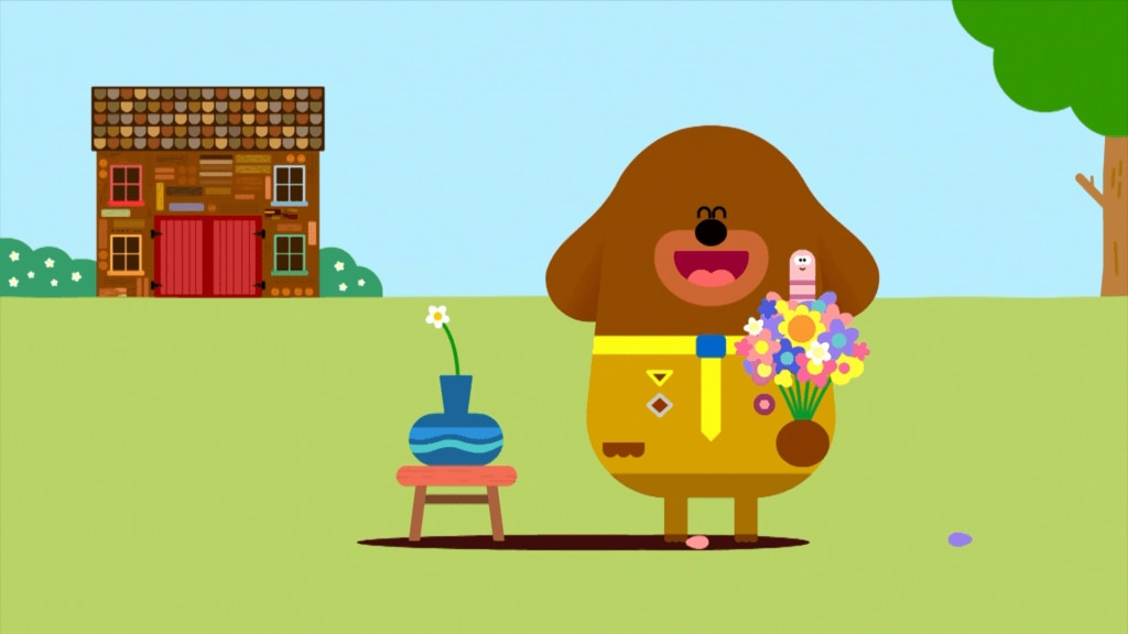 A smiling Duggee the dog holds a bunch of flowers and Worm in the Hiccup Badge